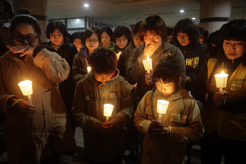 Woohae Cho  |  The Associated Press People gather to pray with candlelights for the missing passengers of a sunken ferry at Danwon High School in Ansan, South Korea, on Thursday. An immediate evacuation order was not issued for the ferry that sank off South Korea's southern coast, likely with scores of people trapped inside, because officers on the bridge were trying to stabilize the vessel after it started to list amid confusion and chaos, a crew member said Thursday.