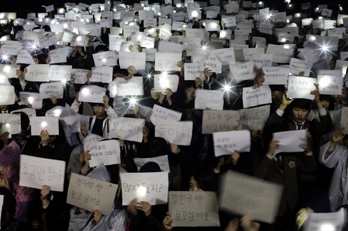 "Danwon High School students hold papers with messages such as ""come back,"" ""miss you,"" ""love you"" and ""don't lose your hope"" for their friends who are missing after Wednesday's ferry disaster at the school yard in Ansan, South Korea, Thursday, April 17, 2014. Strong currents, rain and bad visibility hampered an increasingly anxious search Thursday for 287 passengers, many thought to be high school students, still missing more than a day after their ferry flipped onto its side and sank in cold waters off the southern coast of South Korea. (AP Photo/Woohae Cho)"