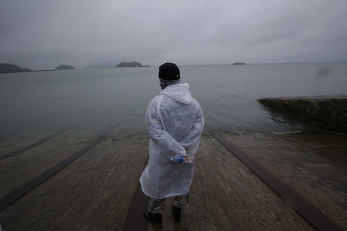 A rescue personal looks at a sea in windy and rainy day at a port in Jindo, south of Seoul, South Korea, Thursday, April 17, 2014. An immediate evacuation order was not issued for the ferry that sank off South Korea's southern coast, likely with about 290 people trapped inside, because officers on the bridge were trying to stabilize the vessel after it started to list, a crew member said Thursday. (AP Photo/Lee Jin-man)