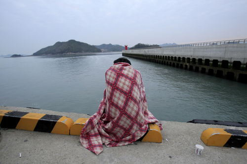 A relative waits for their missing loved one at a port in Jindo, South Korea, Wednesday, April 16, 2014. A ferry carrying 459 people, mostly high school students on an overnight trip to a tourist island, sank off South Korea's southern coast on Wednesday, leaving nearly 300 people missing despite a frantic, hours-long rescue by dozens of ships and helicopters. (AP Photo/Ahn Young-joon)