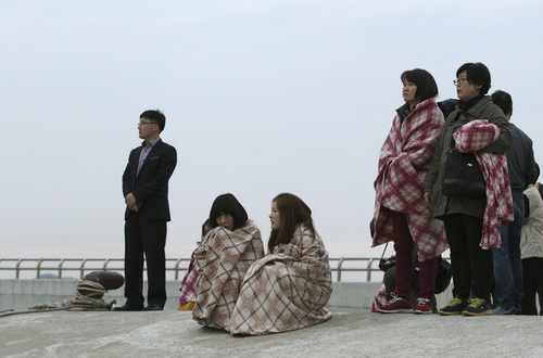 Relatives wait for their missing loved ones at a port in Jindo, South Korea, Wednesday, April 16, 2014. A ferry carrying 459 people, mostly high school students on an overnight trip to a tourist island, sank off South Korea's southern coast on Wednesday, leaving nearly 300 people missing despite a frantic, hours-long rescue by dozens of ships and helicopters. (AP Photo/Ahn Young-joon)