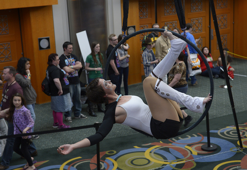 Scott Sommerdorf      The Salt Lake Tribune An aerial performer hangs from a hoop at the Salt Palace during the opening day of Salt Lake Comic Con, Thursday, April 17, 2014.