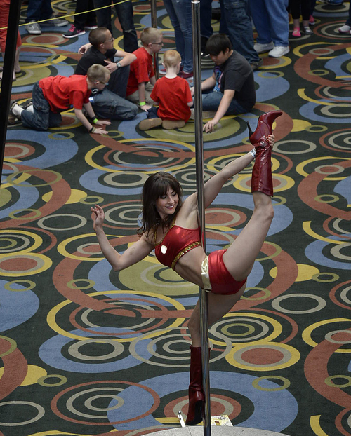 Scott Sommerdorf      The Salt Lake Tribune A group of young boys played a game on the Salt Palace floor as Angela Nelson of Onyx performed on the pole during the opening day of Salt Lake Comic Con, Thursday, April 17, 2014.