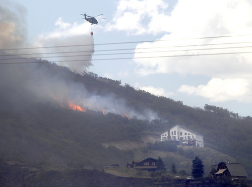 Al Hartmann  |  The Salt Lake Tribune Helicopter makes a water drop on fire coming back to life Wednesday afternoon above homes in Rockport Estates.