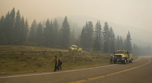 Firefighters are stationed near the Stuart Guard Station in Huntington Canyon on Wednesday, June 27, 2012, to protect the historic building from the Seeley Fire burning in the Manti-La Sal National Forest. (AP Photo/Paul Fraughton, The Salt Lake Tribune)