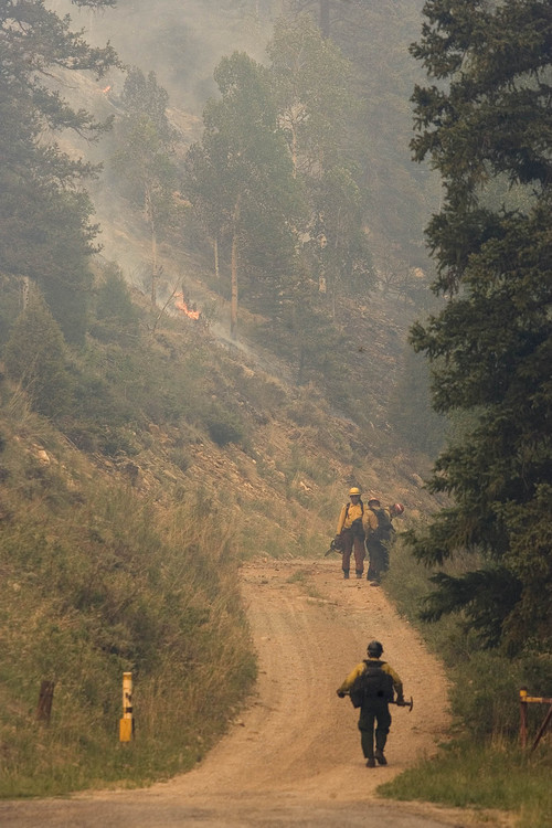 Firefighters work near the historic Stuart Guard Station in Huntington Canyon on Wednesday, June 27, 2012, as the Seeley fire continues to burn in the Manti-La Sal National Forest. (AP Photo/Paul Fraughton, The Salt Lake Tribune)