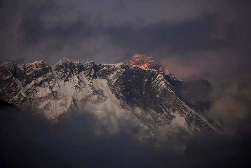 FILE - In this Oct. 27, 2011 file photo, the last light of the day sets on Mount Everest as it rises behind Mount Nuptse as seen from Tengboche, in the Himalaya's Khumbu region, Nepal. An avalanche swept the slopes of Mount Everest on Friday, April 18, 2014, along a route used to ascend the world's highest peak, killing at least six Nepalese guides and leaving nine more missing, officials said. (AP Photo/Kevin Frayer, File)