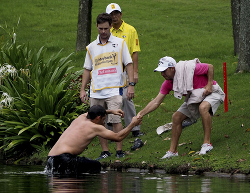 THIS CORRECTS THE SPELLING OF LARRAZABAL -Pablo Larrazabal, left, of Spain is pulled out of a lake after being attacked by a swarm of hornets during the second round of the Malaysian Open golf tournament at Kuala Lumpur Golf and Country Club in Kuala Lumpur, Malaysia, Friday, April 18, 2014. (AP Photo/Joshua Paul)