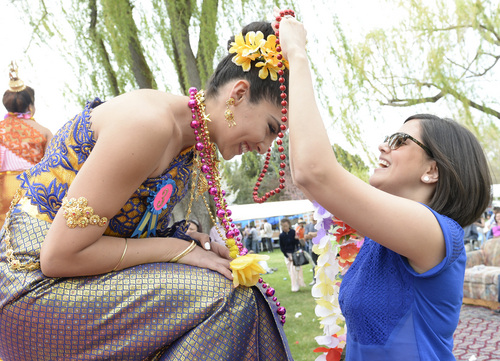 Rick Egan  |  The Salt Lake Tribune  Miss Songkran contestant, Camila Maguna, (left) Dalin Miya (right), at the Songkran Festival at the Wat Dhammagunaram Buddhist Temple in Layton, Saturday, April 19, 2014.    The contestant gets points for the necklaces and flowers awarded to them by the audience members. The contestant with the most points wins the prize for most popular, in the contest.    The annual two day Thai-Lao New Year celebration includes authentic food and music, and the Miss Songkran beauty contest. It continues Sunday at 10 a.m. to 2 p.m, and is open to the public.