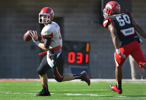 Scott Sommerdorf   |  The Salt Lake Tribune Utah QB Conner Manning escapes the pocket and the rush of DE Pita Taumoepenu during Utah football practice at Rice Eccles Stadium, Saturday, March 22, 2014.