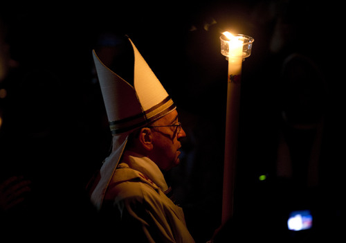 Pope Francis holding a tall, lit, white candle, enters a darkened St. Peter's Basilica to begin the Easter vigil service, at the Vatican, Saturday, April 19, 2014. (AP Photo/Alessandra Tarantino)