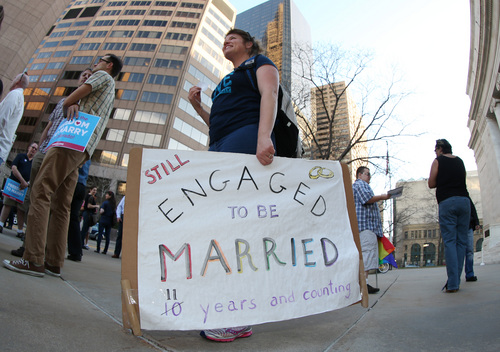 As viewed through a fisheye lens, Anna Simon of Denver carries a sign about the state of her marriage to her partner at a protest outside the Federal Courthouse in downtown Denver on Wednesday, April 9, 2014. The protest, sponsored by Support Marriage Equality in Colorado, was held as a federal appeals court weighs inside the Denver courthouse whether to give an important victory to gay couples' right to marry in Utah and Oklahoma. (AP Photo/David Zalubowski)