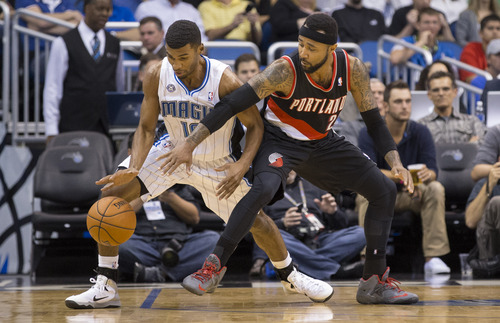 3Orlando Magic's Ronnie Price (10) steals the ball from Portland Trailblazers Mio Williams (25) during the first half of an NBA basketball game in Orlando, Fla., Tuesday, March 25, 2014. (AP Photo/Willie J. Allen Jr.)