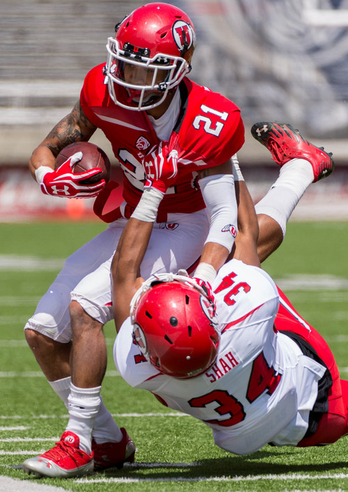 Trent Nelson  |  The Salt Lake Tribune Utah's Troy McCormick is pulled down by Sharrief Shah during the University of Utah's Red & White football game at Rice-Eccles Stadium in Salt Lake City, Saturday April 19, 2014.