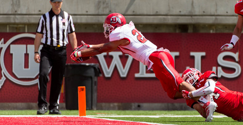 Trent Nelson  |  The Salt Lake Tribune Utah's Devontae Booker dives into the end zone, with Evan Eggiman hanging on during the University of Utah's Red & White football game at Rice-Eccles Stadium in Salt Lake City, Saturday April 19, 2014.