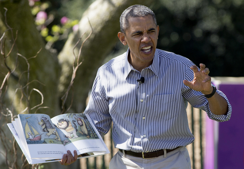 """President Barack Obama makes a face as he reads """"Where the Wild Things Are"""" by Maurice Sendak, during the White House Easter Egg Roll on the South Lawn of the White House is Washington, Monday, April 21, 2014. Thousands of children are gathered at the White House for the annual Easter Egg Roll. This year's event features live music, cooking stations, storytelling, and of course, some Easter egg rolling. (AP Photo/Carolyn Kaster)"""