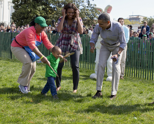 President Barack Obama and first lady Michelle Obama cheer a little egg roller as they host the White House Easter Egg Roll on the South Lawn of the White House is Washington, Monday, April 21, 2014.  Thousands of children gathered at the White House for the annual Easter Egg Roll. President Barack Obama and first lady Michelle Obama kicked off the festivities on the White House South Lawn. This year's event features live music, cooking stations, storytelling, and of course, some Easter egg rolling. (AP Photo/Carolyn Kaster)