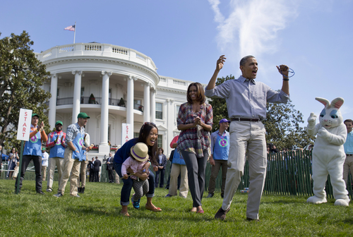 President Barack Obama and first lady Michelle Obama cheer and applaud as they host the White House Easter Egg Roll on the South Lawn of the White House is Washington, Monday, April 21, 2014. Thousands of children gathered at the White House for the annual Easter Egg Roll. President Barack Obama and first lady Michelle Obama kicked off the festivities on the White House South Lawn. This year's event features live music, cooking stations, storytelling, and of course, some Easter egg rolling.(AP Photo/Carolyn Kaster)