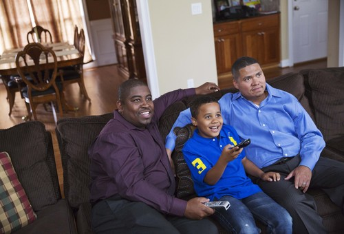 Shelton Stroman, left, and partner Christopher Inniss, right, watch television at home with their son Jonathan, 9, Thursday, April 17, 2014, in Snellville, Ga. A gay rights group on Tuesday, April 22, 2014, filed a federal lawsuit in Atlanta challenging the state of Georgia's constitutional ban on same-sex marriages. Georgia voters in 2004 overwhelmingly approved a constitutional ban on gay marriage in 2004. The ban was challenged in courts by gay rights groups who challenged the wording of the ballot question, but the state Supreme Court ultimately ruled the vote was valid in 2006. (AP Photo/David Goldman)