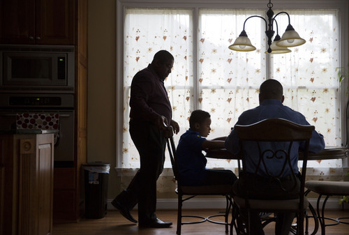 Shelton Stroman, left, and partner Christopher Inniss, right, help their son Jonathan, 9, with homework in the couple's kitchen, Thursday, April 17, 2014, in Snellville, Ga. A gay rights group on Tuesday, April 22, 2014, filed a federal lawsuit in Atlanta challenging the state of Georgia's constitutional ban on same-sex marriages. (AP Photo/David Goldman)