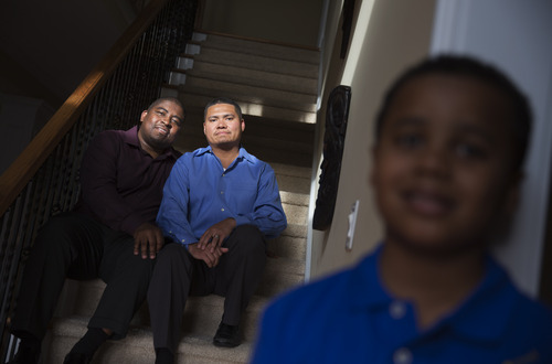 Shelton Stroman, left, sits with partner Christopher Inniss, in their home, as their son Jonathan, 9, looks on at right, Thursday, April 17, 2014, in Snellville, Ga. A gay rights group on Tuesday, April 22, 2014, filed a federal lawsuit in Atlanta challenging the state of Georgia's constitutional ban on same-sex marriages. (AP Photo/David Goldman)