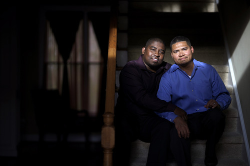 Shelton Stroman, left, sits with partner Christopher Inniss, in their home, Thursday, April 17, 2014, in Snellville, Ga. A gay rights group on Tuesday, April 22, 2014, filed a federal lawsuit in Atlanta challenging the state of Georgia's constitutional ban on same-sex marriages. (AP Photo/David Goldman)