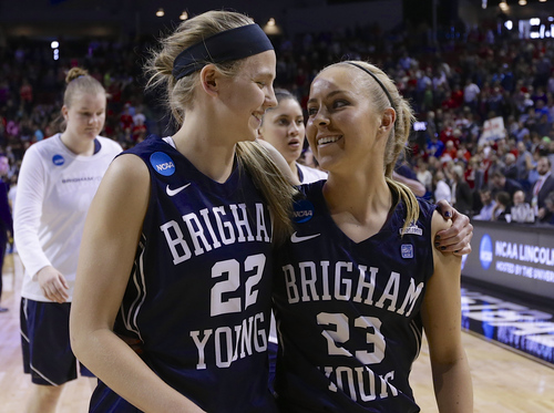 BYU's Kristine Fuller (22) and Makenzi Morrison (23) hug as they walk off the court following a 70-51 loss to Connecticut in a regional semifinal in the NCAA college basketball tournament in Lincoln, Neb., Saturday, March 29, 2014. (AP Photo/Nati Harnik)