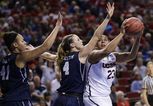 Connecticut's Kaleena Mosqueda-Lewis (23) is defended by BYU's Kim Beeston (4) and Morgan Bailey (41) during the first half of a regional semifinal in the NCAA college basketball tournament in Lincoln, Neb., Saturday, March 29, 2014. (AP Photo/Nati Harnik)