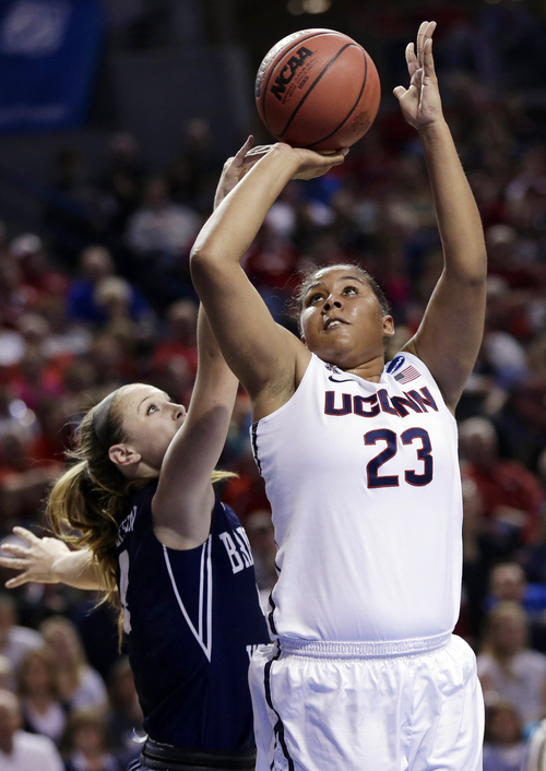 Connecticut's Kaleena Mosqueda-Lewis (23) shoots past BYU's Kim Beeston (4) during the first half of a regional semifinal in the NCAA college basketball tournament in Lincoln, Neb., Saturday, March 29, 2014. (AP Photo/Nati Harnik)