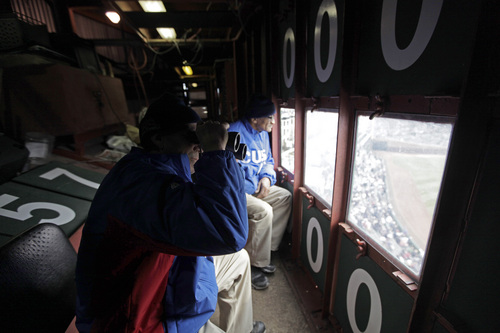 In this April 10, 2014 photo, scoreboard operators Brian Helmus, left, and Fred Washington look out to the field from inside the iconic scoreboard at Wrigley Field during a baseball game between Pittsburgh Pirates and Chicago Cubs, in Chicago. With Boston's Fenway Park and Wrigley the only two stadiums in the majors with primary manual scoreboards, it has been a job largely shrouded in mystery until the Cubs allowed The Associated Press climb the steel ladder through the steel floor of the scoreboard for a rare visit to mark Wrigley's 100-year anniversary. (AP Photo/Kiichiro Sato)