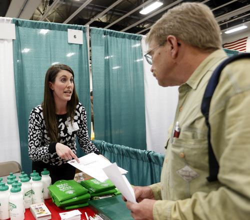 In this April 22, 2014 photo, Erin Wilson, of Hannaford Bros. supermarket company, left, talks with a job seeker during a job fair Columbia-Greene Community College in Hudson, N.Y. The Labor Department releases weekly jobless claims on Thursday, April 24, 2014. (AP Photo/Mike Groll)