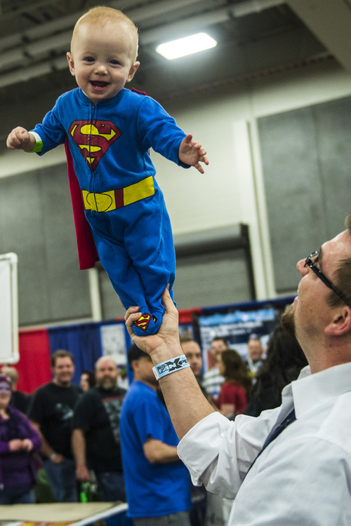 Chris Detrick  |  The Salt Lake Tribune Super Man Deacon Ely, 10 months, flies through the air with the help of his dad Tyler at Salt Lake Comic Con FanXperience at the Salt Palace Convention Center on Saturday.