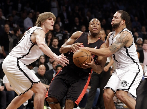 Toronto Raptors' Kyle Lowry drives between Brooklyn Nets' Andrei Kirilenko, left, and Deron Williams during the first half of Game 3 of an NBA basketball first-round playoff series Friday, April 25, 2014, in New York. (AP Photo/Frank Franklin II)