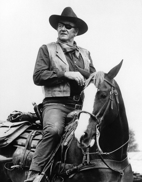 """FILE - This 1969 photo released by Paramount Pictures shows John Wayne in a scene from the movie """"True Grit."""" In mid-20th century America, at least on the surface, there seemed to be an overwhelming consensus of what manhood was all about. The feminist movement that emerged in the 1960s fractured this consensus and fueled significant, though gradual, changes in many Americans' perceptions of gender roles and stereotypes. (AP Photo/Paramount Pictures, file)"""