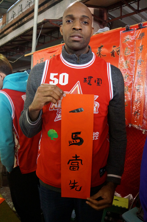 "In this Jan. 17, 2014 photo provided by the Pure Youth Construction basketball team, Quincy Davis III holds a Chinese New Year (Year of the Horse) greeting that reads ""Being The Lead Horse"" in New Taipei City, Taiwan. When the Pure Youth Construction team's owner suggested in 2013 that Davis join Taiwan's national team, he says he found little motivation to keep his U.S. citizenship. ""When you think about who I am as a black guy in the U.S., I didn't have opportunities,"" he says. ""You get discriminated against over there in the South. Here everyone is so nice. They invite you into their homes, they're so hospitable. ... There's no crime, no guns. I can't help but love this place."" (AP Photo/Pure Youth Construction basketball team)"