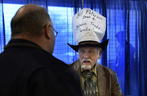 Scott Sommerdorf   |  The Salt Lake Tribune 4th Congressional District candidate Bill Peterson, who altered his cowboy hat into a political sign, talks with Michael Dorsey, left, during a break to count votes at the Utah Democratic Convention, Saturday, April 26, 2014.