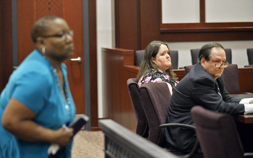 In this April 15, 2014 photo, Rachael Michelle Rapraeger, center, sits with her attorney, Floyd Buford, after Sharon Holmes, left, read her statement to a Houston County Superior Court, in Perry, Ga., during a sentencing hearing.  Rapraeger pleaded guilty this month to 10 misdemeanor charges of reckless conduct and one felony charge of computer forgery after she admitted falsifying hundreds of mammogram reports, one of whom's was Sharon Holmes'. (AP Photo/The Macon Telegraph, Beau Cabell)