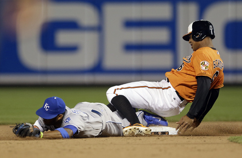 Baltimore Orioles' Jonathan Schoop, right beats the tag at second base as he collides with Kansas City Royals shortstop Alcides Escobar on a grounder by Baltimore's David Lough in the 10th inning of a baseball game, Saturday, April 26, 2014, in Baltimore. Baltimore won 3-2 in 10 innings. (AP Photo/Patrick Semansky)