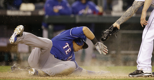 Texas Rangers' Leonys Martin scores on a wild pitch as the tattooed arm of relief pitcher Joe Beimel reaches in too late for a tag in the ninth inning of a baseball game Saturday, April 26, 2014, in Seattle. (AP Photo/Elaine Thompson)