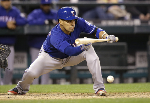 Texas Rangers' Robinson Chirinos hits a sacrifice bunt against the Seattle Mariners in the ninth inning of a baseball game Saturday, April 26, 2014, in Seattle. (AP Photo/Elaine Thompson)