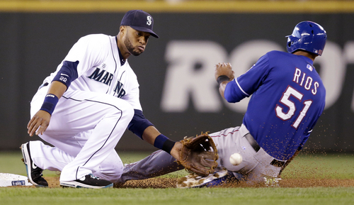 Texas Rangers' Alex Rios (51) slides safely into second on a stolen base as Seattle Mariners second baseman Robinson Cano waits for the ball in the second inning of a baseball game on Saturday, April 26, 2014, in Seattle. (AP Photo/Elaine Thompson)