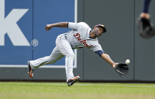 Detroit Tigers right fielder Torii Hunter stretches for a fly ball by Minnesota Twins' Trevor Plouffe during the first inning of a baseball game in Minneapolis, Saturday, April 26, 2014. (AP Photo/Ann Heisenfelt)