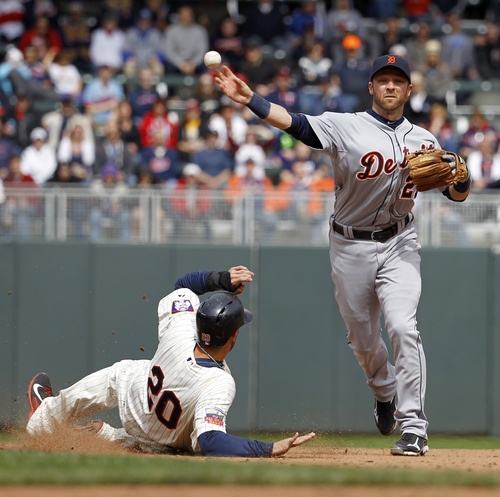 Detroit Tigers shortstop Andrew Romine, right, forces Minnesota Twins' Chris Colabello (20) out at second base as he turns a double play during the fifth inning of a baseball game in Minneapolis, Saturday, April 26, 2014. The Twins' Josmil Pinto was out at first base. (AP Photo/Ann Heisenfelt)