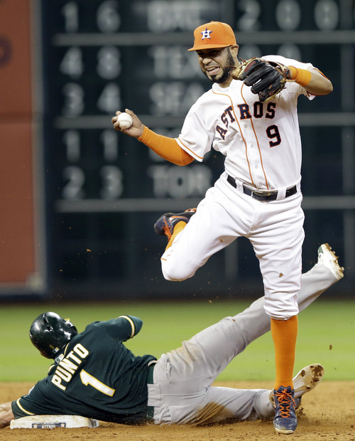 Oakland Athletics' Nick Punto (1) trips Houston Astros shortstop Marwin Gonzalez (9) to break up a double play on Athletics' Coco Crisp in the ninth inning of a baseball game on Saturday, April 26, 2014, in Houston. (AP Photo/Pat Sullivan)