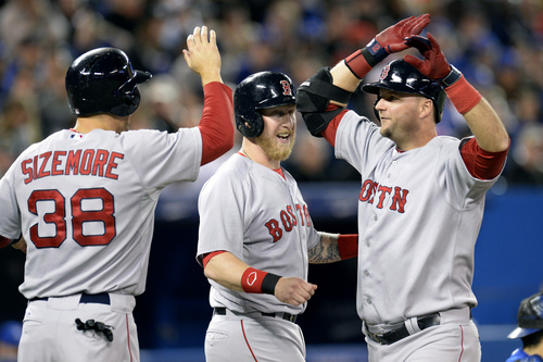 Boston Red Sox's A.J. Pierzynski, right, is congratulated by Mike Carp, center, and Grady Sizemore after hitting a grand slam during the third inning of a baseball game against the Toronto Blue Jays in Toronto on Saturday, April 26, 2014. (AP Photo/The Canadian Press, Frank Gunn)