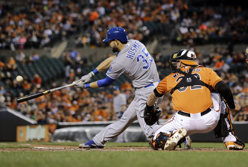 Kansas City Royals' Eric Hosmer doubles in front of Baltimore Orioles catcher Matt Wieters in the third inning of a baseball game, Saturday, April 26, 2014, in Baltimore. Alcides Escobar scored on the play. (AP Photo/Patrick Semansky)