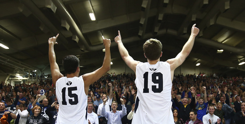 (Jaren Wilkey  |  Courtesy BYU) BYU's (15) Taylor Sander and (19) Devin Young celebrate their second consecutive MPSF Conference Championships with the fans in the Smith Fieldhouse. BYU defeated Stanford 3-0 in the Finals of the MPSF Men's Volleyball Championships hosted by Brigham Young University in Provo on Saturday, April 26, 2014.