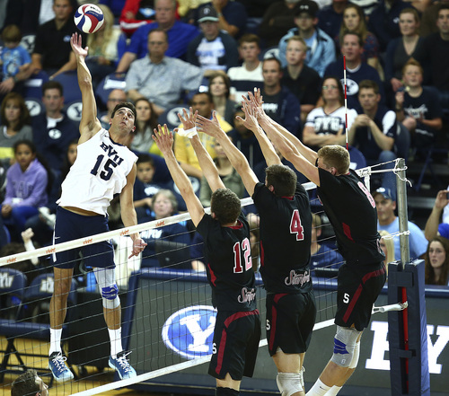 ( Jaren Wilkey  |  Courtesy BYU)  BYU's Taylor Sander spikes the ball past Stanford's (12) Steven Irvin, (4) Conrad Kaminski and (8) James Shaw. BYU defeated Stanford 3-0 in the Finals of the MPSF Men's Volleyball Championships hosted by Brigham Young University in Provo on Saturday, April 26, 2014