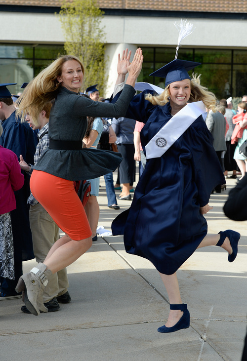 Franciso Kjolseth  |  The Salt Lake Tribune Amelia Hohl, left, gives her sister Lucy Tingey a flying high-five for a family photo as the BYU class of 2014 celebrates following commencement ceremonies at the Marriott Center in Provo on Thursday, April 24, 2014.