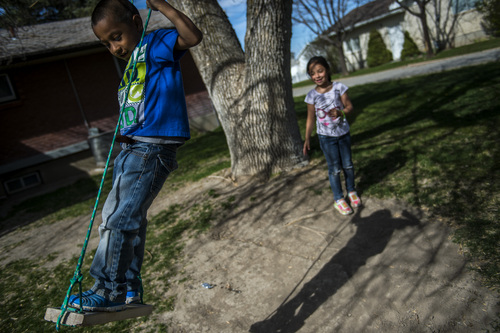 Chris Detrick  |  The Salt Lake Tribune Luis Granda, 8, and Katy Granda, 6, play on a swing at their home in Garland Wednesday April 16, 2014. Part of the family has been ordered to be deported to El Salvador.
